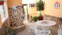 "The patio of ""Hostal Don Vivas"" has a table, chairs and an outdoor shower"